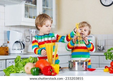 Two funny children cooking italian meal with spaghetti and fresh vegetables in home's kitchen. Sibling children in colorful shirts.