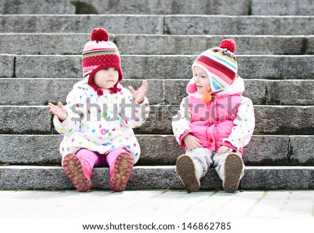 two funny girls sitting on the stairs - stock photo