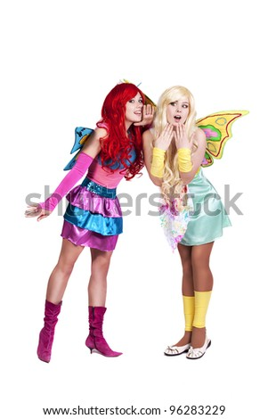 Two funny gossip fairies clown in colorful carnival masquerade dress pixie with wings studio portrait on white background - stock photo