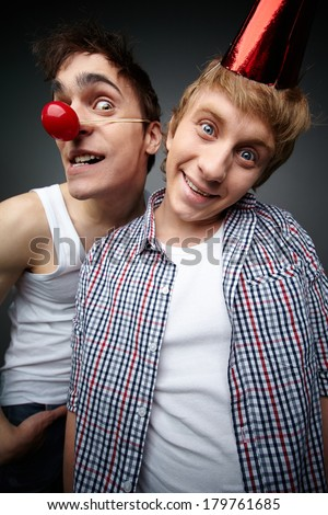 Two funny guys looking at camera and smiling crazily, fools day series - stock photo
