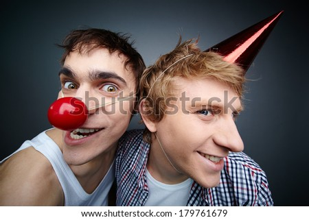 Two funny guys making faces at camera celebrating fools day - stock photo