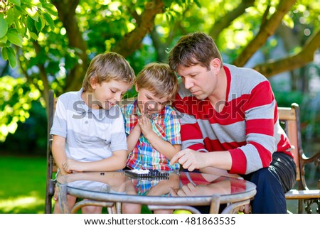 Two funny handsome kid boys and young father playing together checkers game. Sons, siblings children and dad spending leisure together. Family having fun in summer garden outside.