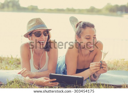 Two funny happy young women friends laughing browsing watching social media videos blogs listen to music on smart pad computer laying outdoors on green meadow on sunny summer day  - stock photo