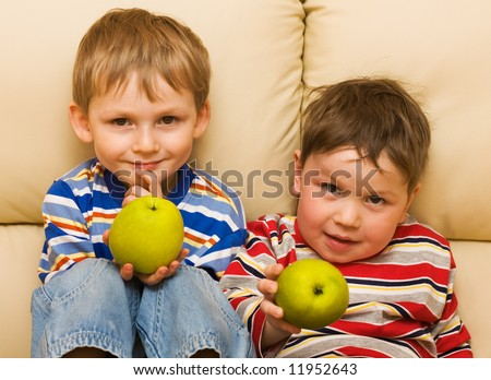 Two funny kids show an apple