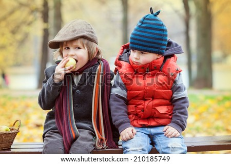 two funny little boy on the bench in autumn Park - stock photo