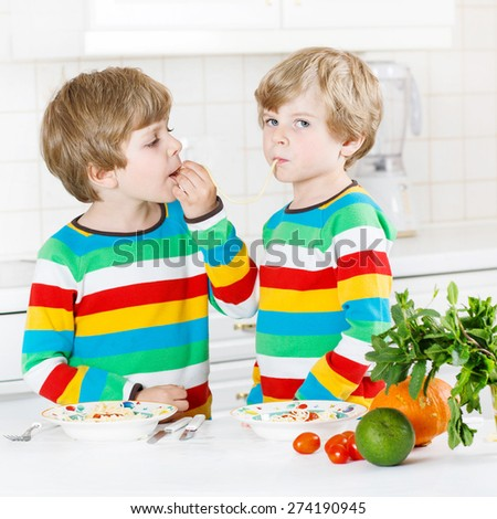 Two funny little boys eating meal with pasta and fresh vegetables in domestic kitchen, indoors. Sibling children in colorful shirts. - stock photo