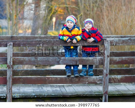 Two funny little kid sibling boys and friends in colorful clothes standing on bridge on spring day. Children having fun together, autumn or winter. Happy, joyful family - stock photo