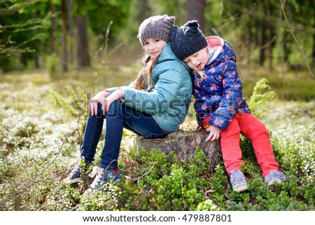 Two funny little sisters having fun during forest hike on beautiful spring day