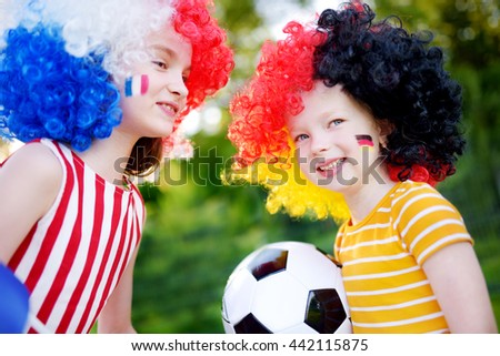 Two funny little sisters supporting and cheering their national football teams during soccer championship - stock photo