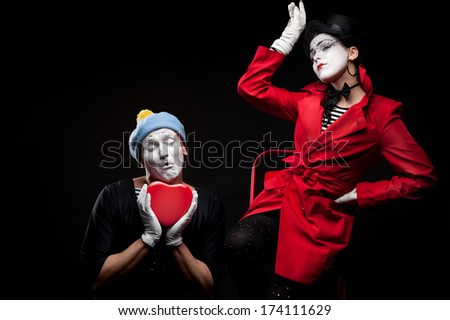 two funny mimes holding red heart isolated on black background - stock photo