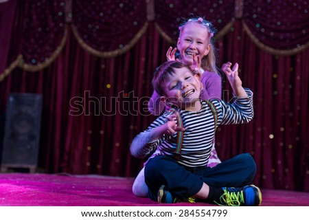 Two funny playful children, boy and girl, smiling while acting as monsters with claws, on a purple stage, in a theatrical representation - stock photo