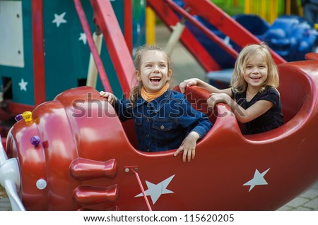 Two funny sisters on carousel ride in red airplane in children's park. - stock photo