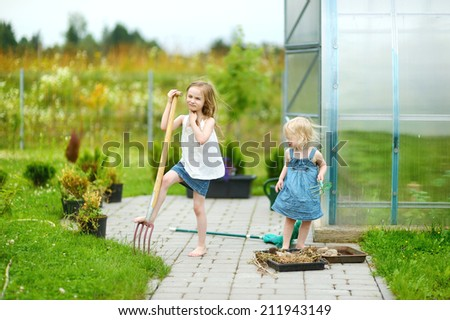Two funny sisters with garden tools on warm summer day