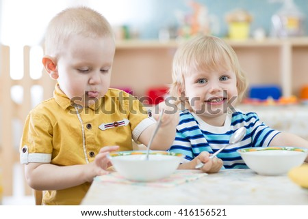 Two funny smiling little kids eating in kindergarten - stock photo