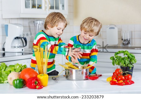 Two funny twin kids cooking italian meal with spaghetti and fresh vegetables in home's kitchen. Sibling children in colorful shirts. - stock photo