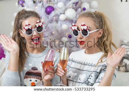 two funny women drinking champagne in decorated for Christmas room