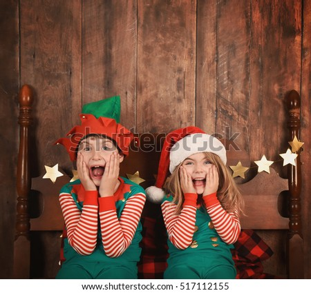 Two funny young children are surprised and excited sitting on a bed with Santa hats on and Christmas pajamas with a wood wall. Use it for a holiday message idea.