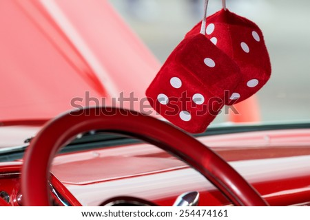 Two fuzzy dice hanging from the rear view mirror on a classic car. - stock photo
