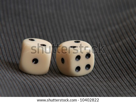 Two gambling dices on gray fabric background