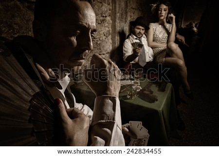 Two gangsters playing poker with their women sitting beside them