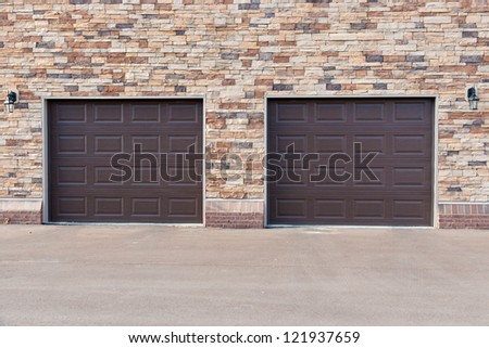 Two garage doors on brick wall in modern appartment building - stock photo