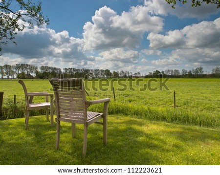 Two garden chairs are overlooking a fresh green agricultural landscape