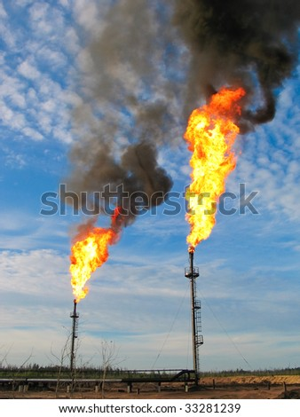 Two gas flares burning and smoking - stock photo