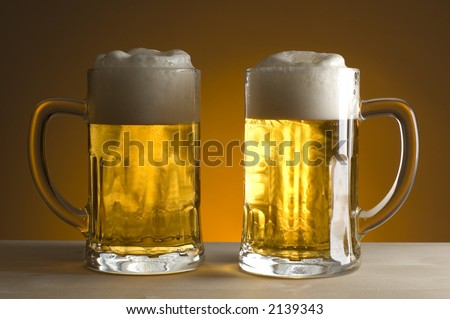 two gasses of beer on orange background close up - stock photo