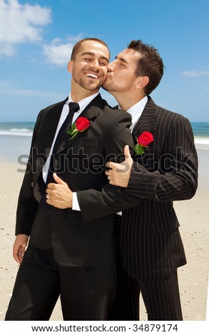 Two gay grooms kissing.  Men in suits. - stock photo