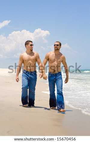 Two gay men in jeans walking on a beach - stock photo