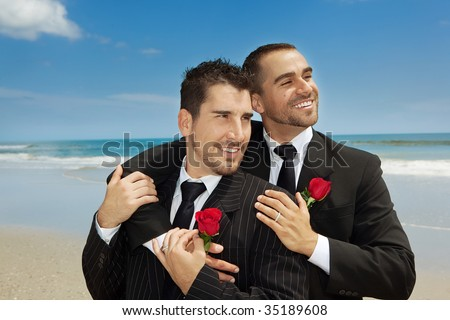 Two gay men married on a beach - stock photo