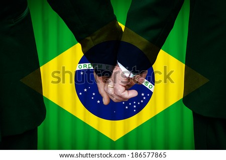 Two gay men stand hand in hand before a marriage altar featuring an overlay of the flag colors of Brazil, having just been legally married under the Same-Sex Marriage legislation of that country.   - stock photo