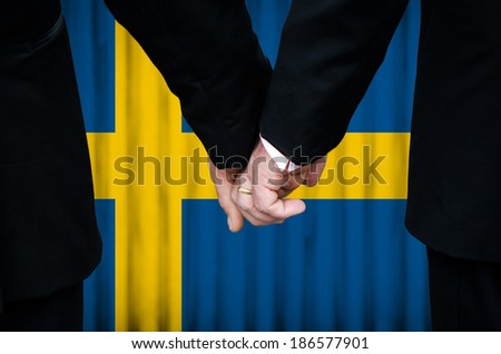 Two gay men stand hand in hand before a marriage altar featuring an overlay of the flag colors of Sweden, having just been legally married under the Same-Sex Marriage legislation of that country.    - stock photo