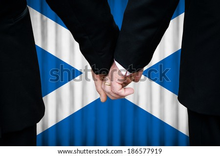 Two gay men stand hand in hand before a marriage altar featuring an overlay of the flag colors of Scotland, having just been legally married under the Same-Sex Marriage legislation of that country.    - stock photo