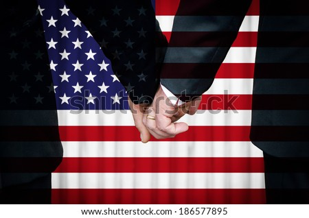 Two gay men stand hand in hand before a marriage altar overlaid with the flag of the United States of America, having just been married within a State that has legalized Same-Sex Marriage legislation. - stock photo