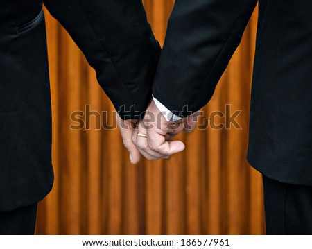 """Two gay men stand hand in hand before the marriage altar having just been legally married under Same-Sex Marriage legislation.  Their bodies form the shape of the letter """"M"""".  - stock photo"""