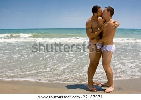 Two gay men standing at the beach, kissing - stock photo