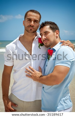 Two gay men standing on a beach after wedding ceremony - stock photo
