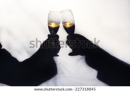 Two gay men toasting their wedding with champagne.  Silhoette taken outdoors behind a screen, with abstract shapes of trees and foliage blurred in background.   - stock photo