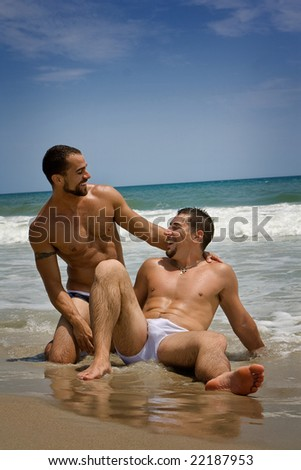 Two gay men vacationing at the beach - stock photo
