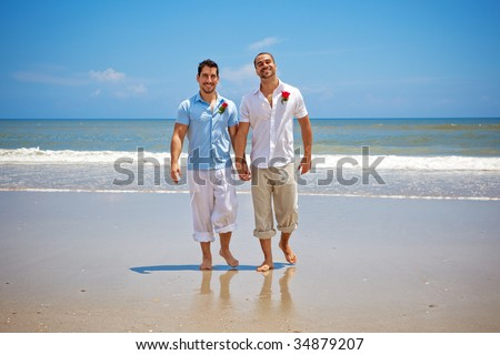 Two gay men walking on a beach after wedding ceremony - stock photo