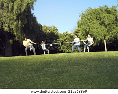 Two generation family playing tug-of-war on grass in park, side view