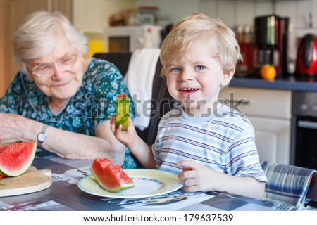 Two generations: Little boy and his great grandmother eating watermelon in home kitchen. Selective focus on child - stock photo