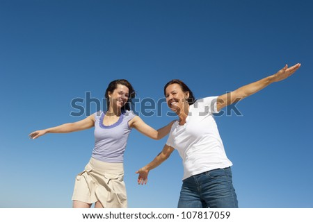 Two generations of women, mother and daughter, posing on a sunny day outdoor, with happy smiles and joyful, with clear blue sky as background and copy space. - stock photo