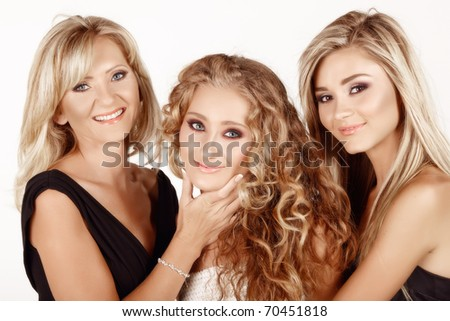two generations of women: mother in her 40s with a beautiful teenage and young adult daughters with different hairstyles. Real life family. - stock photo
