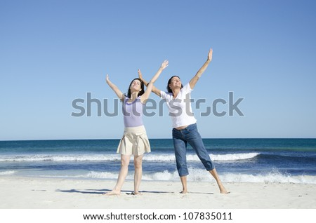 Two generations, two women, mother and daughter happy together at the beach, in a cheerful mood with arms up, isolated with wide open ocean and clear blue summer sky as background and copy space. - stock photo