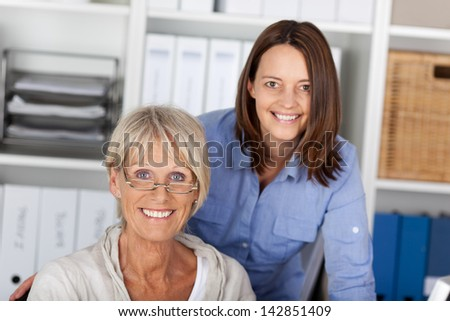 Two generations, younger and older cheerfully posing inside the office. - stock photo
