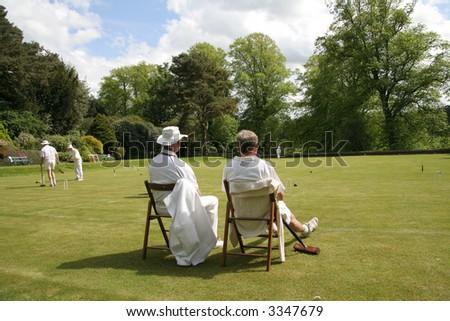 Two gentlemen sit watching a croquet match - stock photo