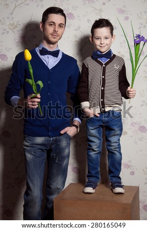 Two gentlemen: young father and his little cute son. man is holding yellow tulip. blue-eyed boy with purple flower. Studio shot - stock photo