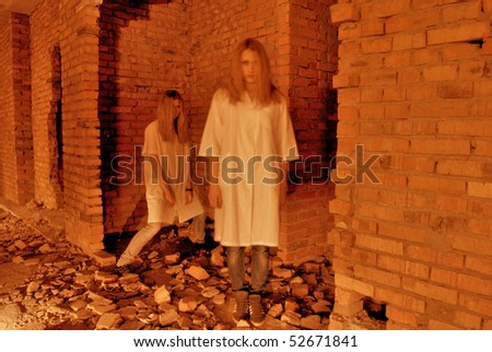Two ghosts of  young girls in abandoned building ruins - stock photo